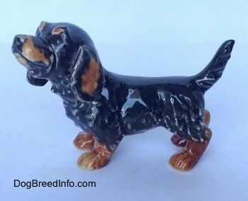 The left side of a black and brown Dachshund figurine in a standing pose. The figurine has short detailed furry legs.