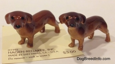 The front left side of two Dachshund Mama standing figurines. The figurines have long bodies and short legs.