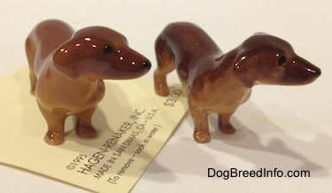 Two Dachshund Mama standing figurines have ears that are hard to differentiate from there bodies.