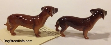The right side of two Dachshund Mama standing figurines. It is hard to tell the difference between the tail of the figurine from the body.