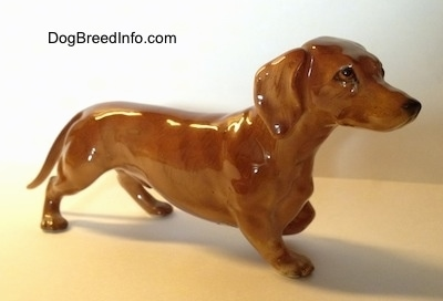 The front right side of a pointing porcelain Dachshund figurine. The figurine is very detailed.