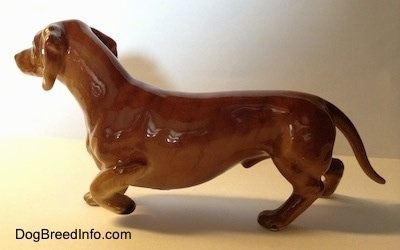 The left side of a brown porcelain Dachshund pointing figurine. The figurine has a long body, short legs and a long tail.