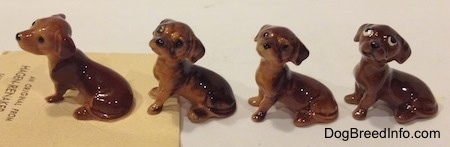 The left side of four different Dachshund Pup Seated figurines. The details in the figurines eyes vary.