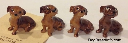 The front left side of four Dachshund Pup Seated figurines. The figurines lack paw details.