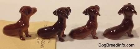 The right side of four Dachshund Pup Seated figurines. The figurines are glossy.
