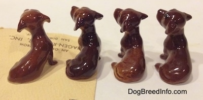 The back side of four Dachshund Pup Seated figurines. The tails of the figurines are hard to differentiate from the body.