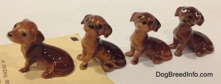 Four different Dachshund Pup Seated figurines have long tails relative to there sides.