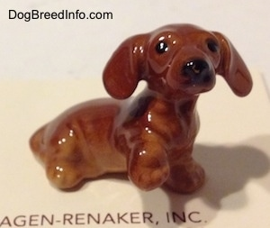 The right side of a Dachshund Puppy Seated Paw Up figurine. The ears of the figurines are sticking out.
