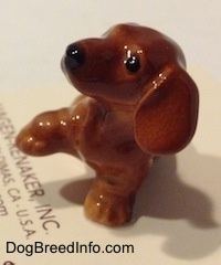 Topdown view of a Dachshund Puppy Seated Paw Up figurine. The figurine has big wide paws.
