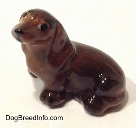 Topdown view of a Dachshund sitting figurine. The ears of the figurine are attached to the body.