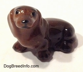 The front left view of a Dachshund sitting figurine. The figurine has black circles for eyes and a nose.