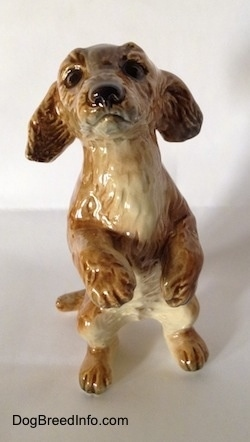 A porcelain figurine of a tan Dachshund in a begging pose. The figurine has accurate face details and its paws are in the air.