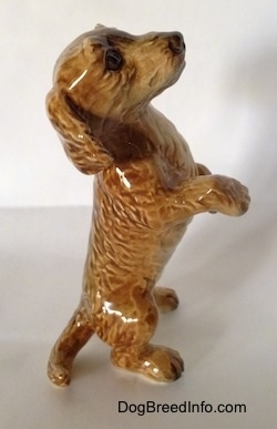 The right side of a tan porcelain Dachshund figurine that is in a begging pose. The figurine has a medium sized tail.