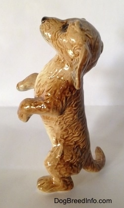 The left side of a porcelain figurine that is a tan Dachshund in a begging pose. The figurine has a long body and fine hair details.