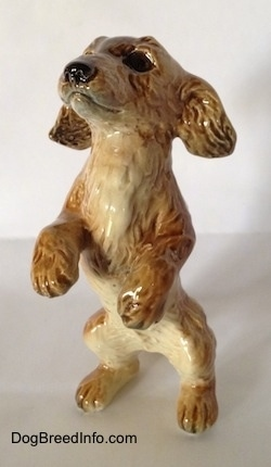 A tan porcelain Dachshund figurine that is in a begging pose. The figurine has detailed furry paws.