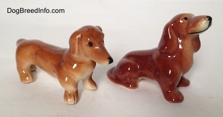 The front right side of two diifferent Dachshund figurines. Both Dachshunds have black circles for eyes.