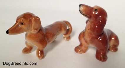 The front left side of a sitting Dachshund and a standing Dachshund figurine. The ears of the figurines are hard to differetiate from there bodies.