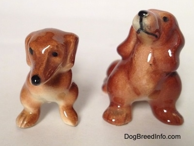 Two different Dachshund figurines, one figurine is sitting and the other is standing. The figurines have short legs.