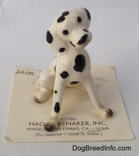A hand painted Dalmatian figurine in a sitting position. The Dalmatian has black circles for eyes.