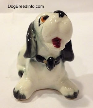 A Dalmatian puppy figurine that looks cartoon-y. The figurine has black tipped paws.