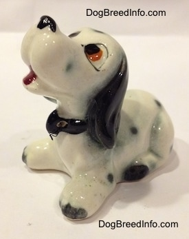 The front left side of a Dalmatian puppy figurine. The figurine has an open mouth and it is wearing a collar.