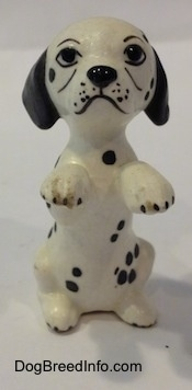 A Dalmatian puppy figurine that is in a begging pose. The figurine has cartoony painted on details.
