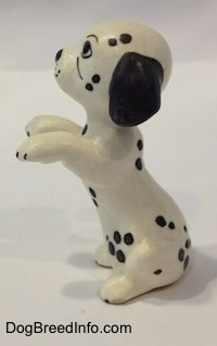 The left side of a Dalmatian puppy figurine that is in a begging pose. The figurine has black ears and short appendages.