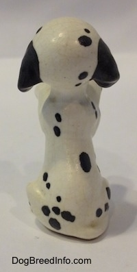 The back of a Dalmatian puppy figurine that is in a begging pose. The figurines tail is hard to differentiate from its body.