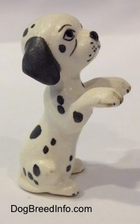 The right side of a figurine that is a Dalmatian puppy in a begging pose. It is hard to differentiate the tail of the figurine from its body.