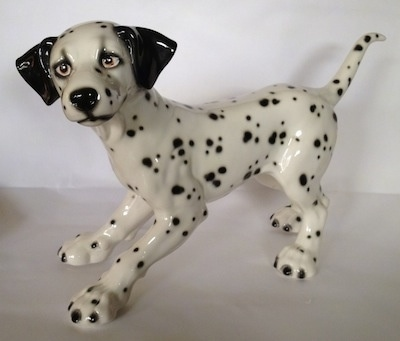 The left side of a Dalmatian figurine. The figurine has a long legs and big paws.