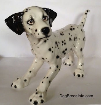 The front left side of a detailed Dalmatian figurine that has long limbs and a long body.