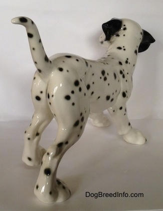 The back right side of a Dalmatian figurine. The figurine is glossy and it has black ears. The tail is long and up in the air. The dog has black spots all over its body.