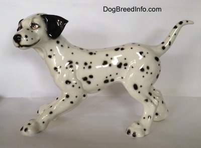 The left side of a Dalmatian figurine. The figurine has a smile painted on its face.