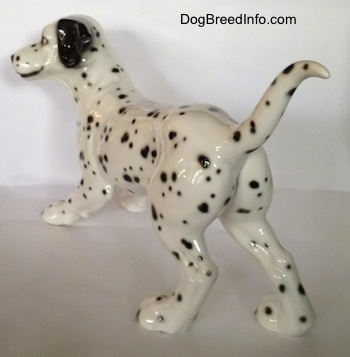 The back left side of a figurine that is of a Dalmatian. The figurine has a detailed face and large ears.