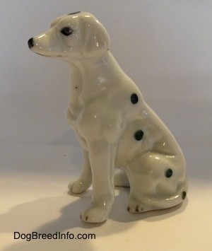 The left side of a Dalmatian puppy in a sitting pose figurine. Its ears are hard to differentiate from its body.