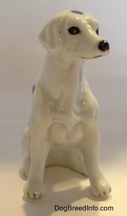The front of a Dalmatian puppy in a sitting pose figurine. The figurine has a detailed chest and it black nails at the top of its paws.