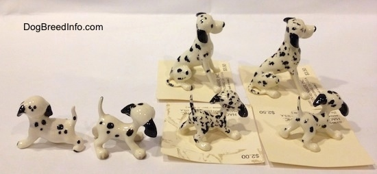 The side of six Dalmatian figurines that all have black ears.