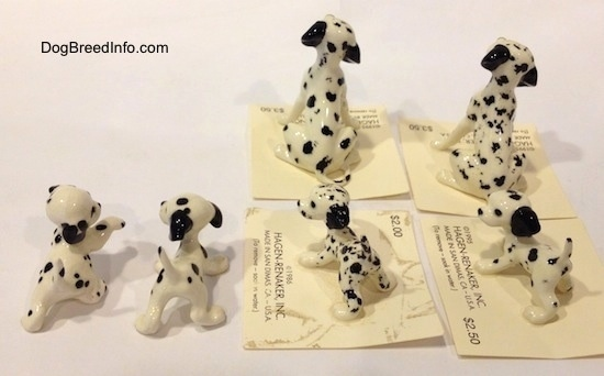 The back of six Dalmatian figurines, two are full grown Dalmatians and four are puppies. The puppies have long tails that are arching up and the full grown figurines have thin tails.