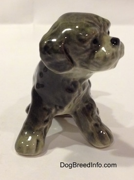 A figurine of a black and gray Dandie Dinmont Terrier puppy that is in a sitting position. It is hard to differentiate the ears of the figurine from the head.