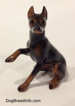 The left side of a black and brown Doberman Pinscher with its paw up figurine. The figurine has a very detailed face.