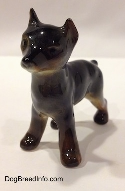 The front left side of a Doberman Pinscher puppy figurine. The figurine has short legs and small paws.
