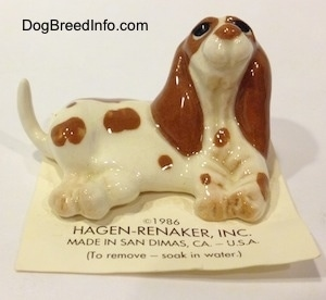 A figurine of a white with brown Curbstone Setter in a lying pose. The figurine is laying on top of a card and its head is in the air.