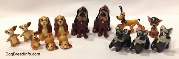 A line-up of fifteen dog figurines that are of famous Disney dog characters.