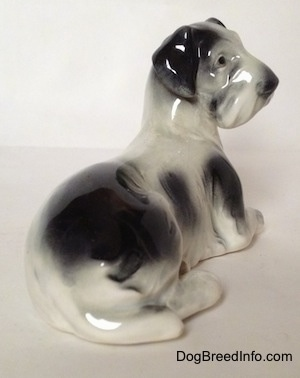 The back right side of a white and black Doxie figurine that is laying down. The figurine has a tail that is hard to differentiate from its body. It has small black eyes and a boxy looking snout.