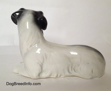 The left side of a figurine of a white and black Doxie laying down.