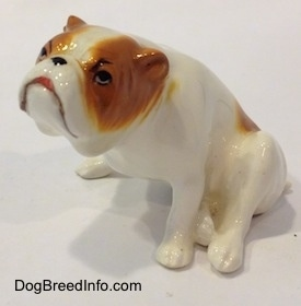The front left side of a white with red Bulldog figurine that is in a sitting pose. The mouth of the figurine is painted like it is open.
