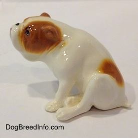 The left side of a white with red Bulldog figurine that is in a sitting pose. The figurine is glossy.