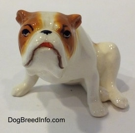 A white with red Bulldog figurine that is in a sitting pose. The figurine has cartoon style eyes.