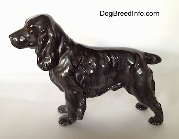 The left side of a blue roan English Cocker Spaniel figurine. The figurine has a small tail.