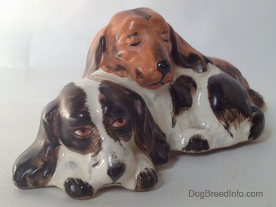 The front left side of a figurine that is two English Cocker Spaniel dogs that are laying down. The figurines are different colors the dog on the bottom is brown and white and the dog on top is orange and black.